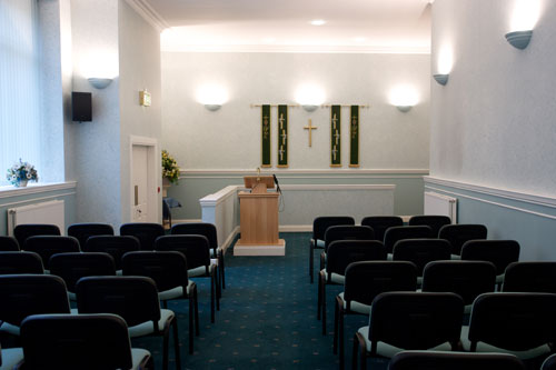 A room set up for a funeral service with a cross on the wall